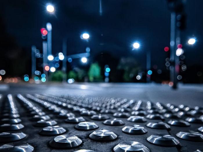 Close-up of illuminated lighting equipment on street at night