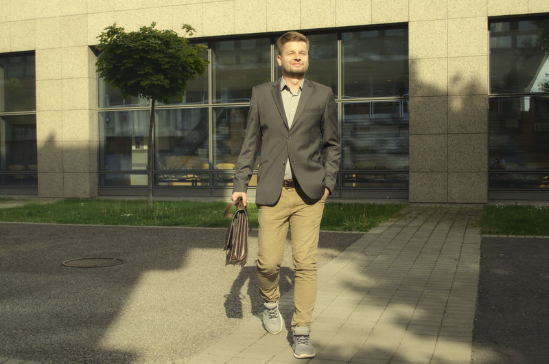 Young businessman with briefcase walking on footpath against office building