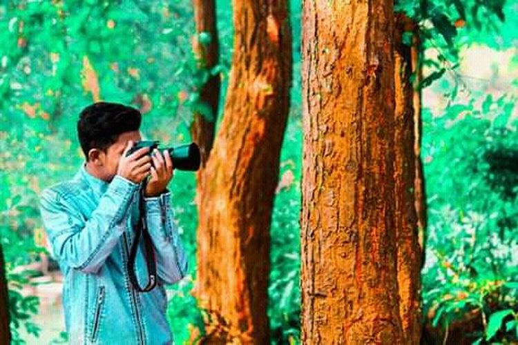 Full length of man photographing through mobile phone in forest