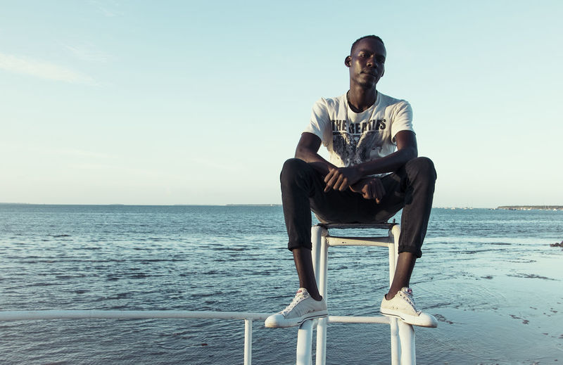 Water Sea Sky Young Adult One Person Young Men Sitting Horizon Leisure Activity Front View Real People Full Length Casual Clothing Nature Lifestyles Day Clear Sky Horizon Over Water The Portraitist - 2019 EyeEm Awards