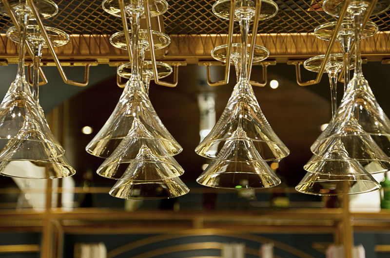 Low angle view of martini glasses in rack at bar