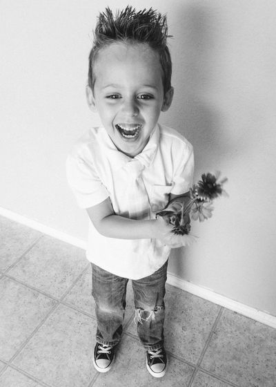 Black And White Boy Casual Clothing Child Cute Front View Full Length Happy Holding Flowers Jeans Joy Kid Laughing Lifestyle Monochrome One Person Person Portrait Smiling Sneakers Spiked Hair Sweet Tie Youth