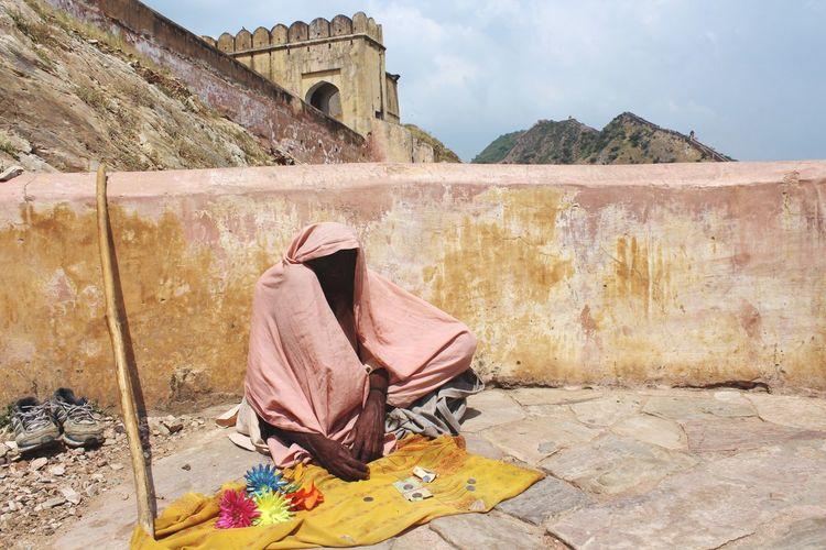 Beggar sitting by retaining wall