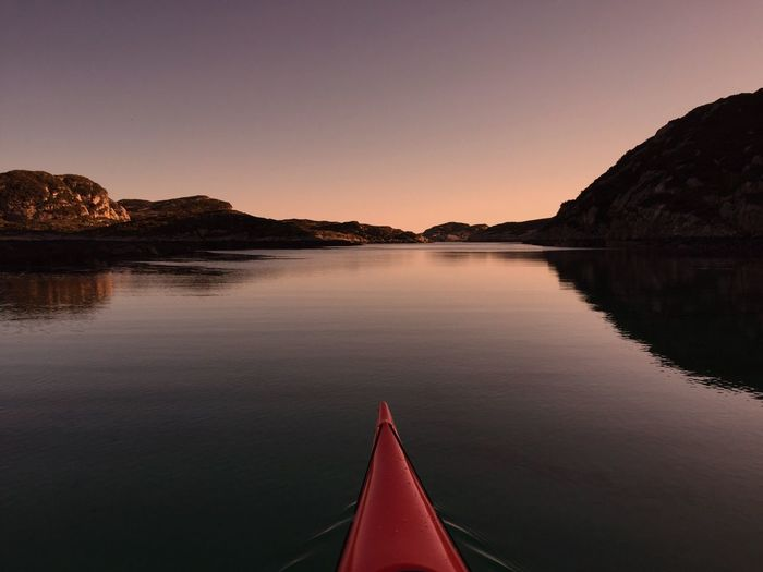 Cropped kayak on calm lake against sky during sunset