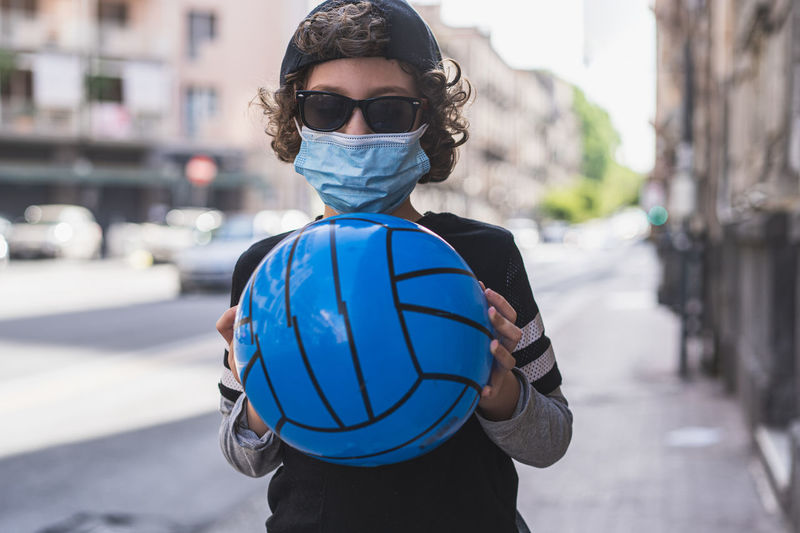 Portrait of boy wearing sunglasses holding ball while standing on street