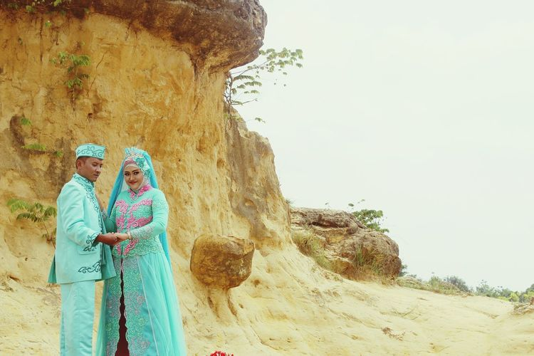 Man and woman wearing traditional clothing while standing by rock formation