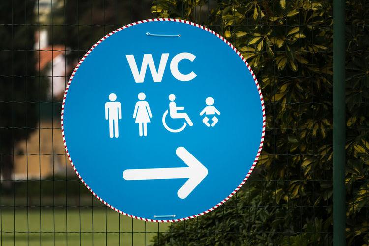 Close-up of restroom sign on fence