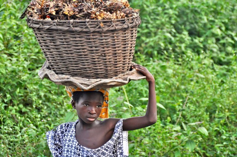 Young woman carrying plants in wicker basket