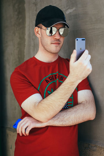 Portrait of man photographing with mobile phone