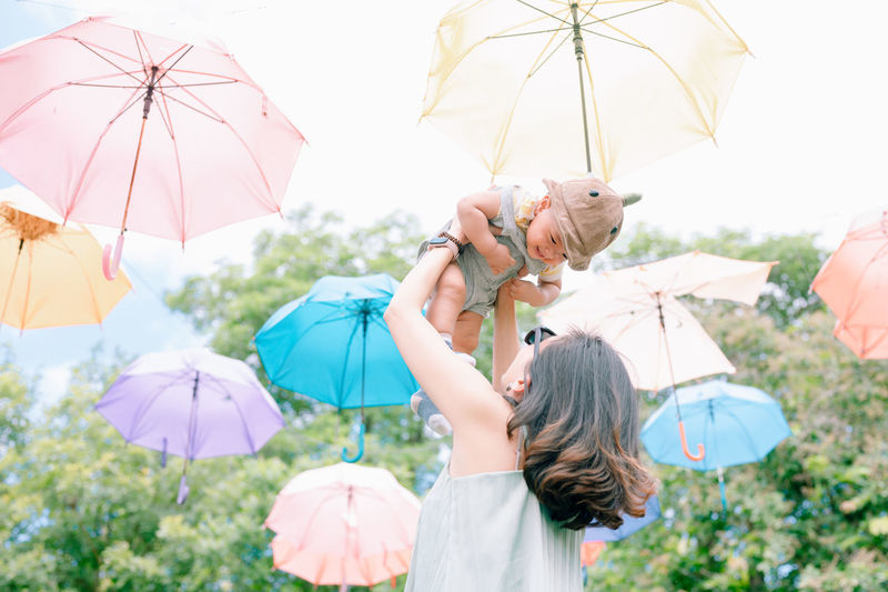 Low angle view of mother picking up son under umbrellas