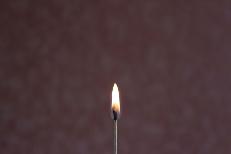 Close-up of burning matchstick against wall