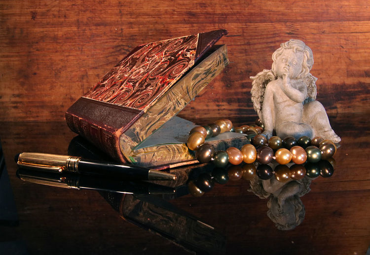 Close-up of book with angel figurine and pearl jewelry on table