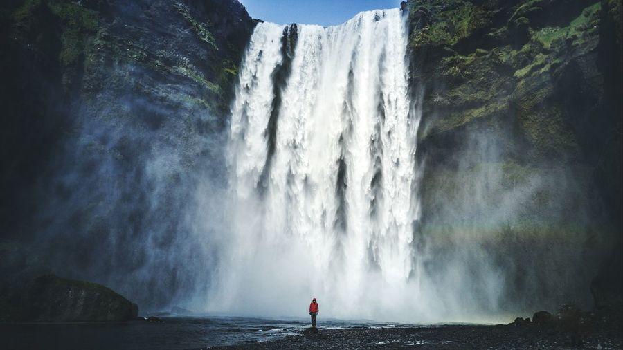 Person standing against beautiful waterfall