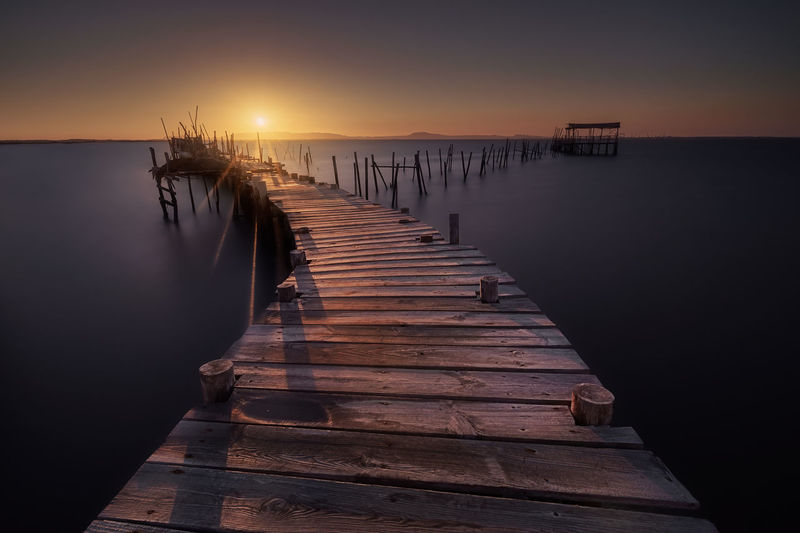 The famous wooden docks in Carrasqueira (Portugal) Water Sky Wood - Material Pier Sunset Tranquility No People Scenics - Nature Tranquil Scene Direction The Way Forward Sea Nature Reflection Wood Wood Paneling Built Structure Outdoors Wooden Post Marina Long Beauty In Nature Carrasqueira Portugal Algarve