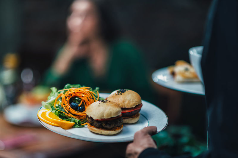 Vegetarian Dinner Vegetarian Food Vegetarian Burger Restaurant Waiter Hand Plate Freshness Serving Colorfoul Waiting Food And Drink Food Lifestyle Delicious Tasty Lunch Dinner Vegetarian Restaurant One Person Holding Ready-to-eat Table Sitting Burger