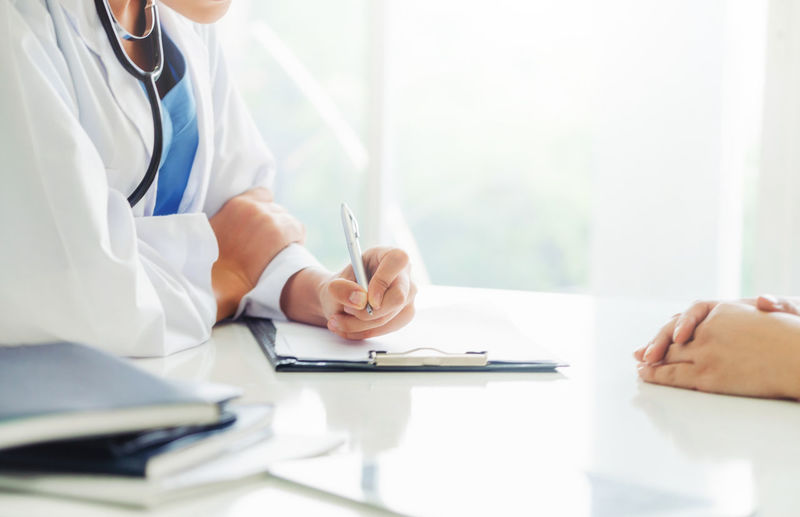 Midsection of doctor and patient discussing on table