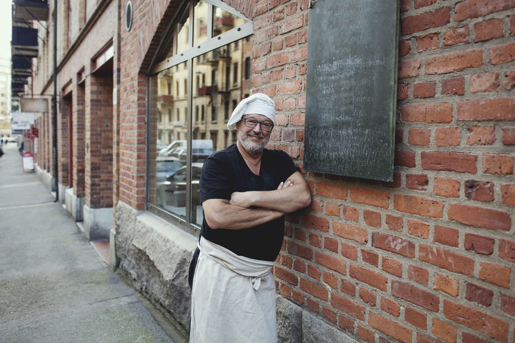 Full length portrait of man standing against brick wall
