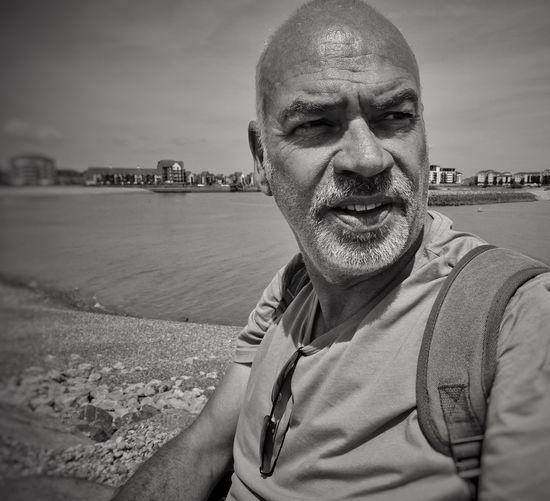 Man Looking Away While Sitting At Beach