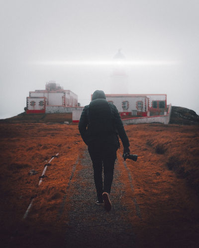 Neist Point Rear View Full Length One Person Real People Architecture Walking Sky Lifestyles Leisure Activity Nature Built Structure Day Outdoors Fog Building Exterior Women Solitude Land Warm Clothing Lighthouse Skye Skye Island Isle Of Skye Scotland Neist Point