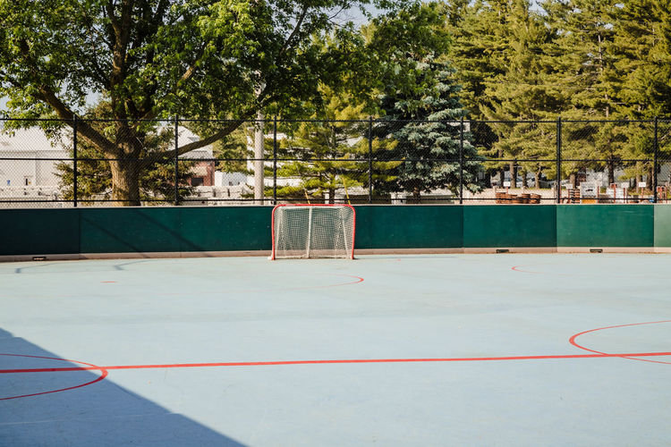 A view a goal of an unoccupied roller hockey rink in a city park