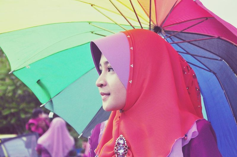 Side View Of Woman In Hijab While Holding Umbrella