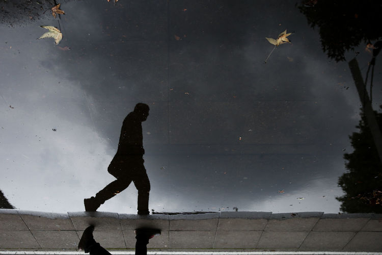 Low angle view of silhouette man reflection on puddle against sky