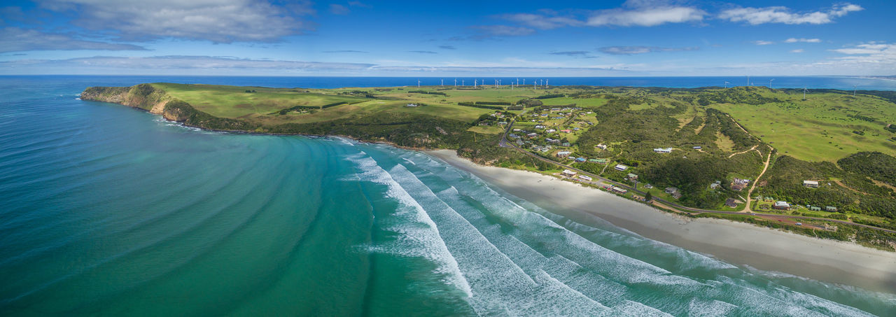 Aerial panorama of Cape Bridgewater beach, settlement, and wind farm in Victoria, Australia Aerial View Beauty In Nature Cloud - Sky Day Green Color Horizon Over Water Landscape Nature No People Outdoors River Scenics Sky Travel Destinations Water