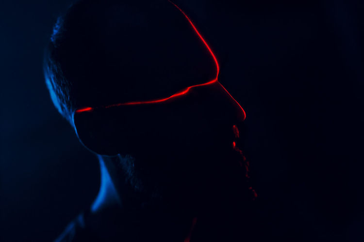 Close-up portrait of silhouette man against black background