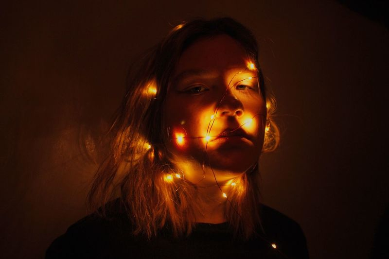 Close-up portrait of young woman with illuminated string lights in darkroom