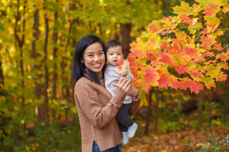 Portrait o smiling young woman with daughter in park