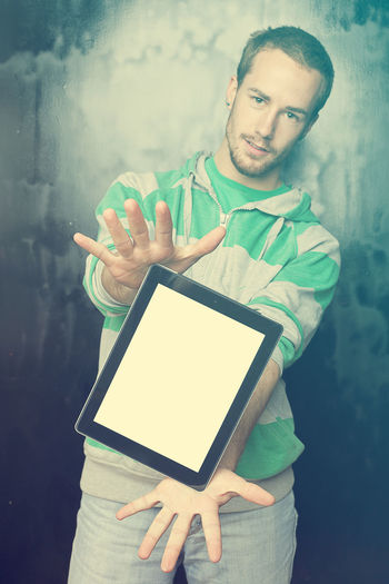Portrait Of Young Man Showing Digital Tablet While Standing Against Old Wall