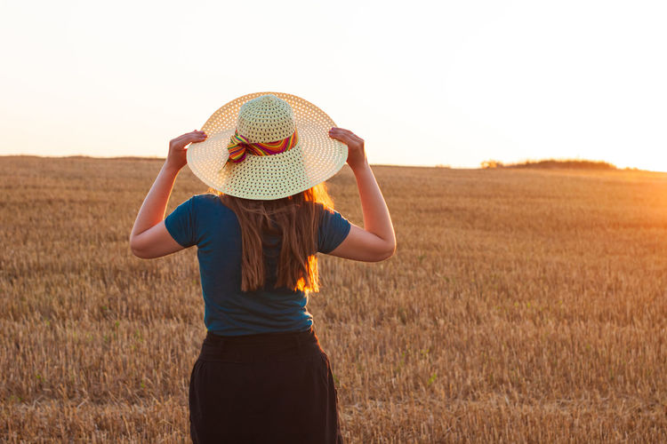 Adorable young girl in summer wheat field in straw hat. woman with long hair countryside sunset