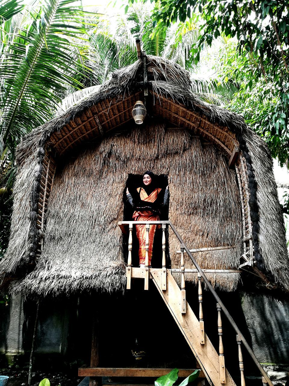 built structure, architecture, low angle view, building exterior, thatched roof, history, real people, outdoors, day, lifestyles, standing, one person, tree, nature, young adult, people