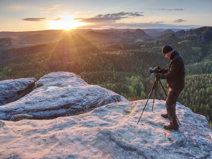 Amateur photographer prepare equipment for taking photos with tripod and camera. spring sunrise
