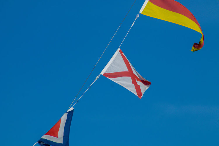 Navigational signal flags flying in the mast Blue Clear Sky Day Environment Flag Flying Freedom Low Angle View Mid-air National Icon Nature No People Outdoors Patriotism Pride Red Sky Waving Wind