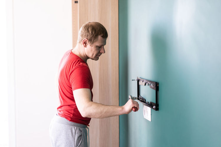 Side view of man standing against wall at home