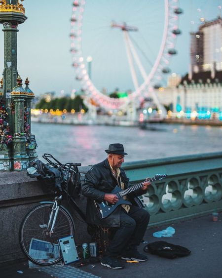 tune Street Performer Guitarist Guitar London London Streets Londonlife Evening Solotraveler Solo Money Life Eyeem Market EyeEm Selects EyeEmBestEdits Fresh On Eyeem  Fresh On Market 2018 City Ferris Wheel Arts Culture And Entertainment Urban Skyline Full Length Arch Bridge