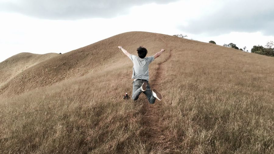 Rear View Full Length Of Playful Man Jumping With Arms Raised Over Hill