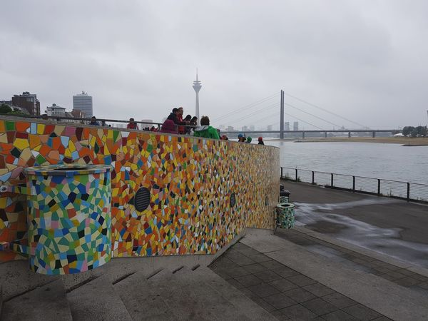 Düsseldorf Tour De France Tourism People Watching Race Cycling Rainy Foggy Skyline City Life Architecture Wall Façade Mosaic Bridge River Tower Dustbins Stairs Not Looking At The Camera Colorful Romantic Landscape Houses Travel Destinations Traveling Stories From The City