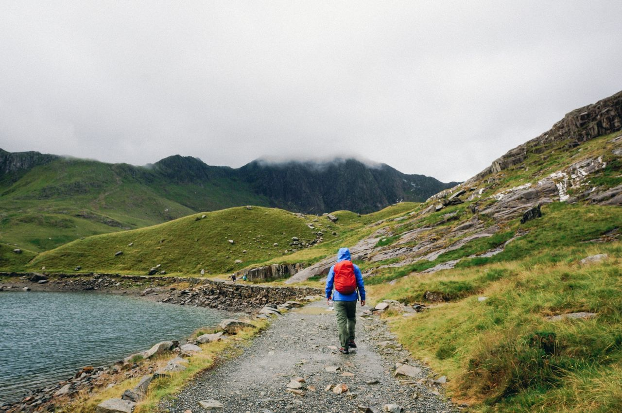 Man walking by mountains against sky