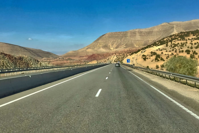 Street through the Atlas mountains at Chichaoua in Morocco. Atlas Car Chichaoua Day Morocco Mountain Road Mountains No People Outdoors Plants Sighn Sky Street The Way Forward Winding Road