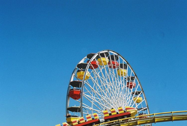 Low Angle View Of Rollercoaster And Ferris Wheel Against Clear Blue Sky