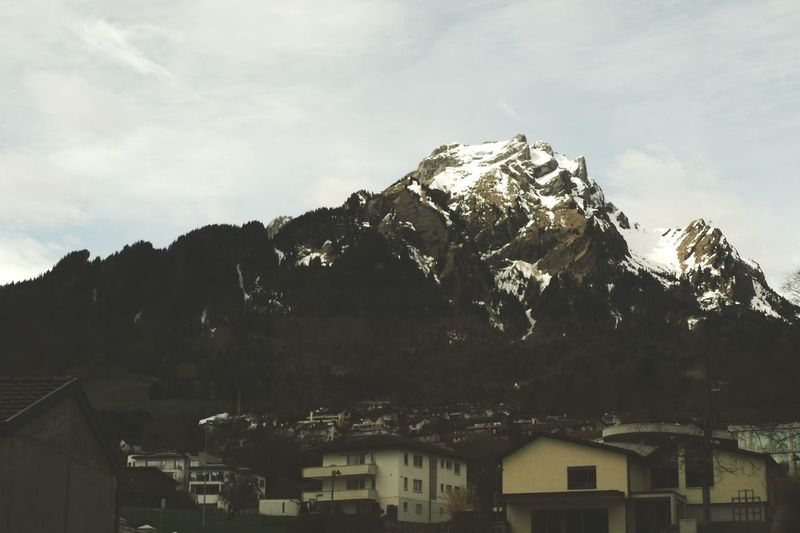 Low angle view of mountain range against cloudy sky