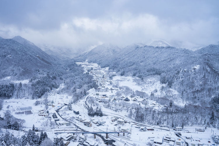 Snow Cold Temperature Winter Mountain Scenics - Nature Environment Nature Landscape Beauty In Nature Cloud - Sky No People Transportation Architecture City Tree Travel Mode Of Transportation Day Motor Vehicle Mountain Range Outdoors Snowcapped Mountain Ski Resort  Snowing