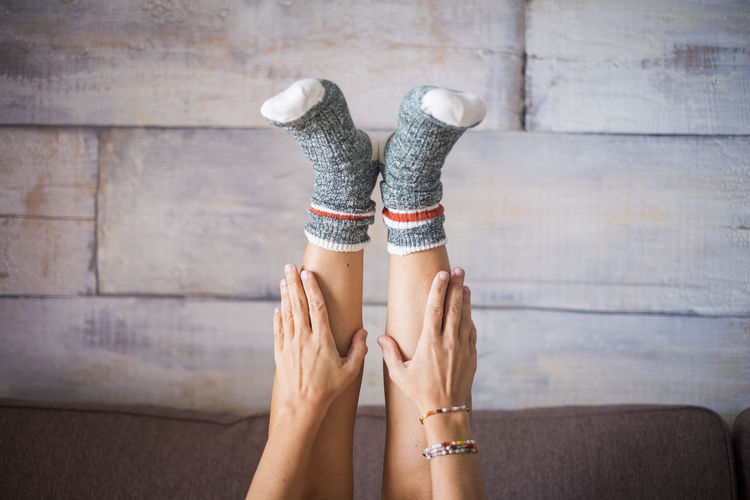 close up of white woman legs with nice socks at home Foot Adult Body Part Bracelet Domestic Room Fashion Hand Human Body Part Human Foot Human Hand Human Leg Human Limb Indoors  Jewelry Lifestyles Low Section People Shoe Sitting Socks Togetherness Women Young Adult Young Woman