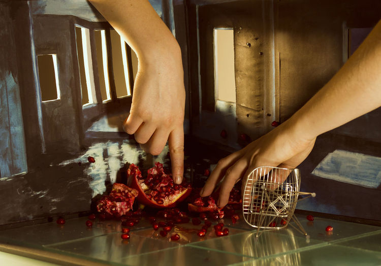 Woman touching crushed pomegranate in a diorama