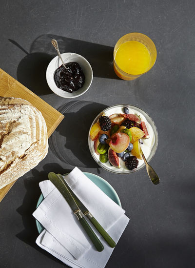 Overhead view of a fruit salad and yoghurt breakfast with bread and orange juice. Bread Breakfast Directly Above Food Food And Drink Freshness Fruit Fruit Salad Healthy Eating High Angle View Indulgence Meal Orange Juice  Outdoors Ready-to-eat Serving Size Setting Still Life Yoghurt