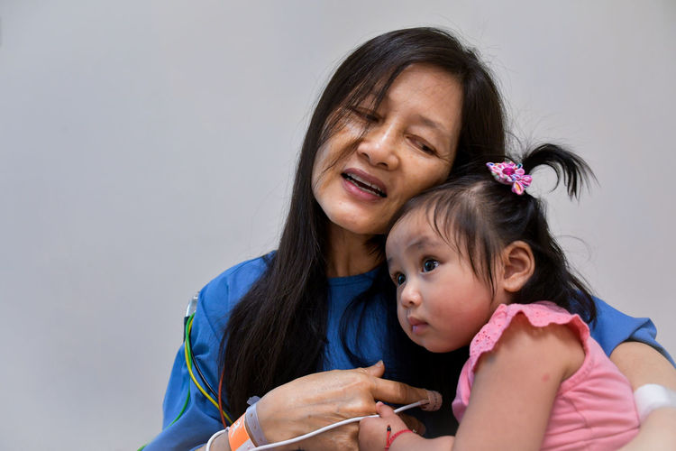 Grandmother With Granddaughter Against Wall At Hospital