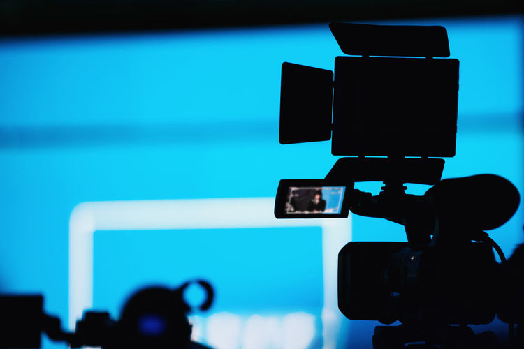Camera Recording Presentation of a Speaker Media Press Conference Silhouette Camera Speaker News Reportage Presentation Communication Public Event Technology Equipment Speech Meeting Seminar Television Politician Politics Entertainment Bussiness Jurnalist Government Stage Corporate Live Leadership Campaign Correspondent Broadcast Blue Camera - Photographic Equipment Digital Camera Unrecognizable Person