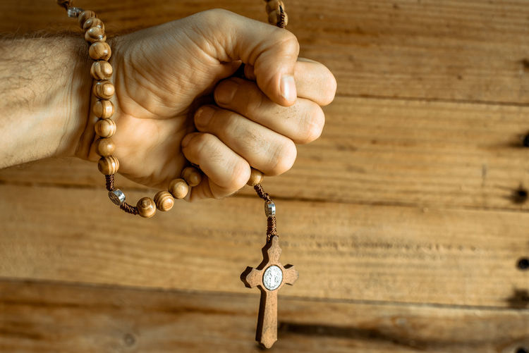 Close-up of hand holding rosary